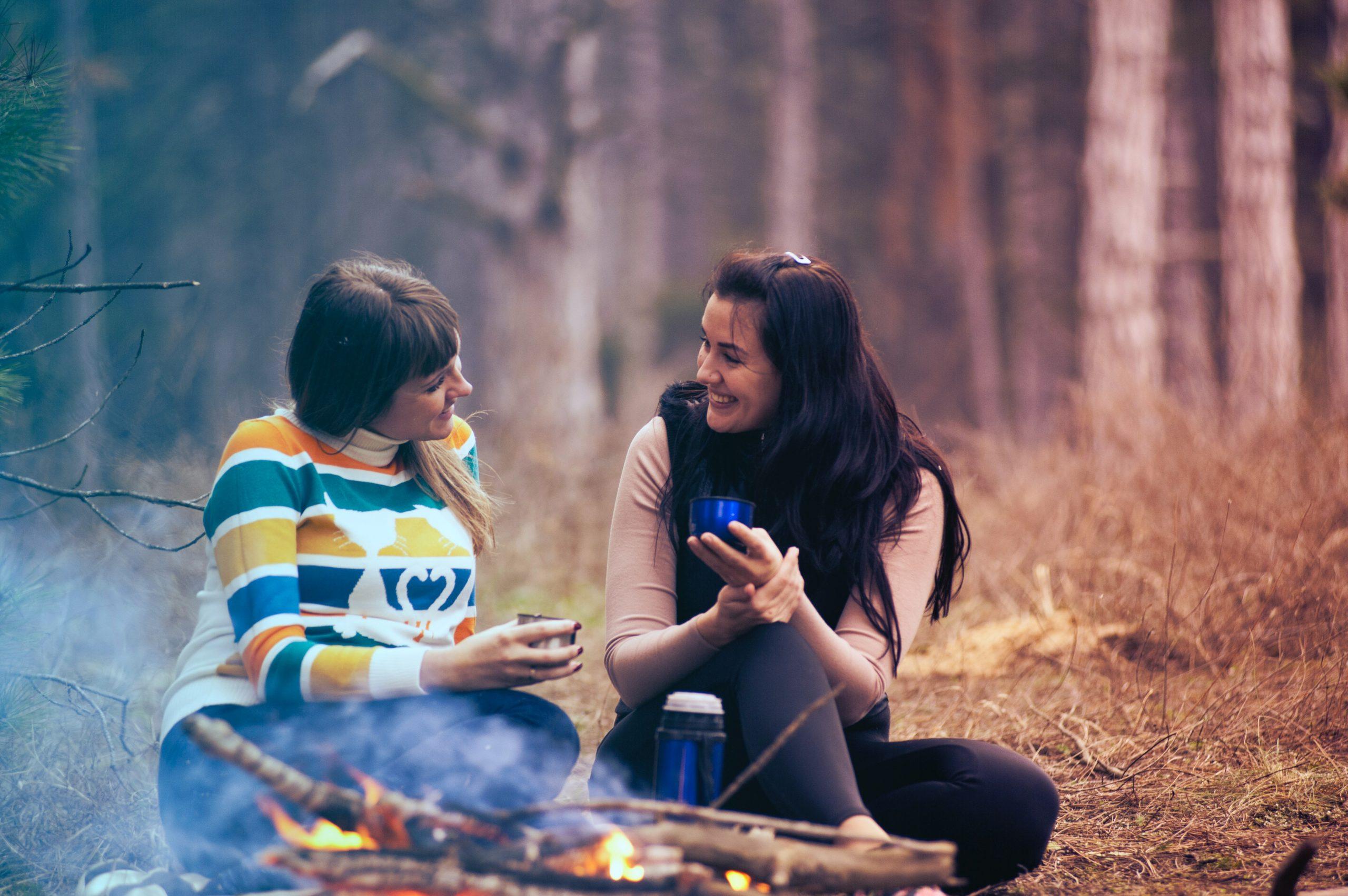 Par de amigas conversando en medio del bosque con un café en la mano